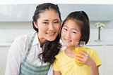 Girl holding orange juice with her mother in kitchen