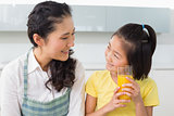 Young girl holding orange juice with her mother in kitchen
