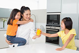 Girl offering her mother a glass of orange juice in kitchen