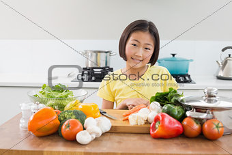 Cute young girl with raw vegetables at the kitchen counter