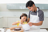 Man with his daughter preparing dough in kitchen