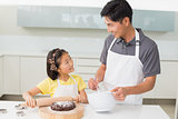 Smiling man with his daughter preparing cookies in kitchen