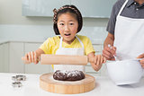 Shocked girl with her father preparing cookies in kitchen
