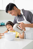 Man with daughter using electric whisk into bowl in kitchen