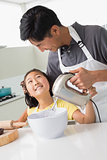 Man with his daughter using electric whisk into bowl in kitchen