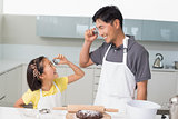 Girl and father holding cookie molds in kitchen