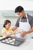 Man with his daughter preparing cookies in kitchen