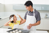 Cheerful girl with her father preparing cookies in kitchen