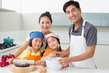 Family of four preparing cookies in kitchen