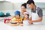 Happy family of four preparing cookies in kitchen