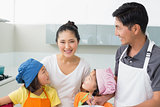 Happy family of four smiling in kitchen