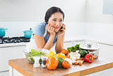 Woman using mobile phone in front of vegetables in kitchen