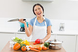 Thoughtful smiling woman chopping vegetables in kitchen