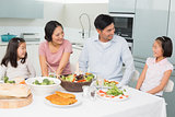 Cheerful family of four enjoying healthy meal in kitchen