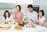 Young family of four enjoying healthy meal in kitchen