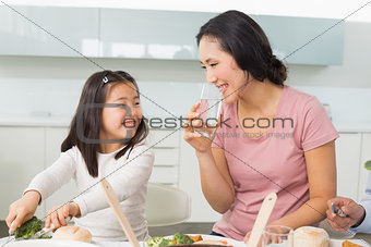 Little girl and mother eat food in kitchen