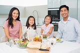 Happy family of four enjoying healthy meal in kitchen