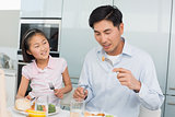 Little girl watching father eat food with a fork in kitchen
