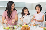 Woman with two little girls having food in kitchen