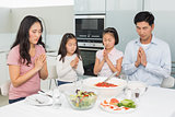 Family of four saying grace before meal in kitchen