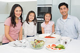 Smiling family sitting at dining table in kitchen