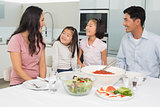 Smiling family of four sitting at dining table in kitchen