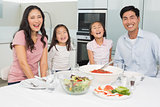 Portrait of a smiling family sitting at dining table in kitchen