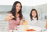 Little girl watching happy woman serve spaghetti in kitchen