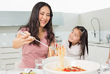 Girl watching happy woman serve spaghetti in kitchen