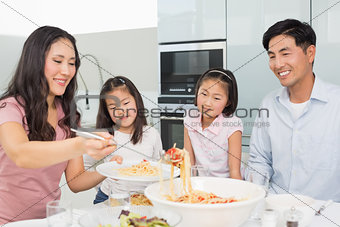 Woman serving food for the family in kitchen