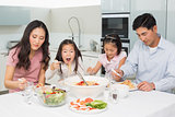 Happy family of four enjoying spaghetti lunch in kitchen