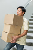 Young man carrying boxes against staircase
