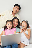 Happy shocked family of four using laptop