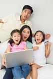 Portrait of shocked family of four doing online shopping