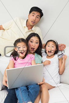Portrait of shocked family of four doing online shopping