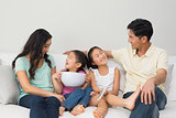 Happy family of with remote control and bowl on sofa in living room