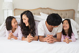 Cheerful family of four lying in bed