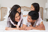 Loving family of four lying in bed at home