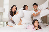 Family of four having pillow fight on bed