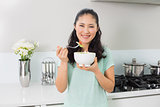 Smiling young woman with a bowl of salad in kitchen