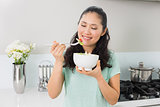 Smiling woman with a bowl of salad in the kitchen