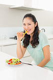Portrait of a young woman eating salad in kitchen