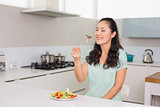 Happy young woman eating salad in kitchen