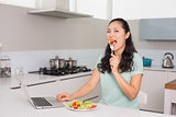 Young woman with laptop eating salad in kitchen