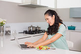 Young woman using laptop while having salad in kitchen