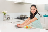 Woman using laptop while having salad in kitchen