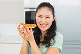 Smiling young woman eating a slice of pizza in kitchen