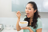 Young woman eating cereals in kitchen