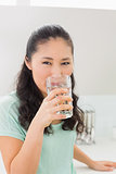 Close-up of a young woman drinking water in kitchen