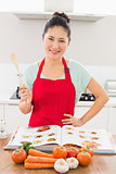 Smiling woman with recipe book and vegetables in kitchen